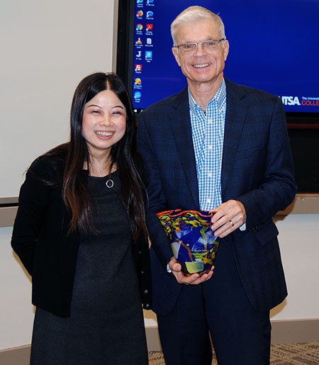 Melody Lo presents Ken Weiher with his retirement gift.