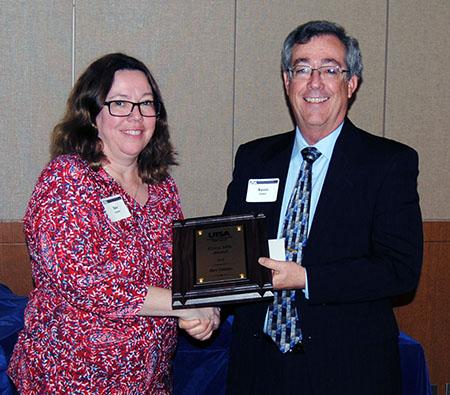 Bev Ostmo receives her award from Associate Dean Kevin Grant.