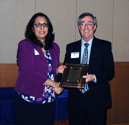 Rosa Garza-Girdy receives her award from Associate Dean Kevin Grant.